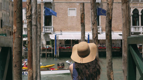 Woman with a hat sitting on a pier in Venice, Italy Footage