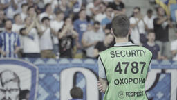 A man guard at the stadium watches the audience. Security Live Action