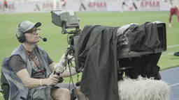 TV broadcast of a sports event. Cameraman with a camera in the stadium Footage