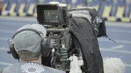 A man cameraman with a camera during a TV broadcast at the stadium Footage