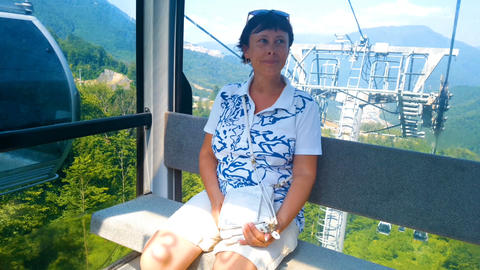 Woman sits in a chair on a cable car 画像