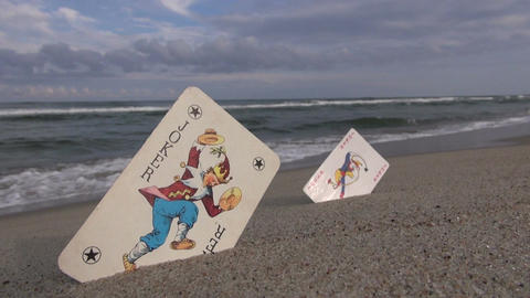 Two playing cards jokers on beach sand near sea Footage