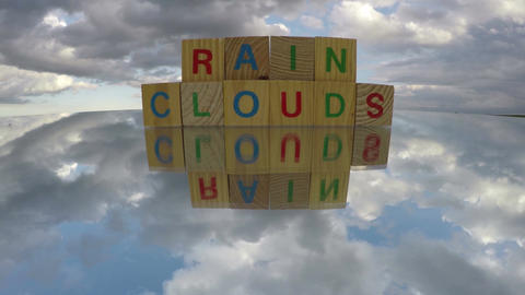 Alphabetical wooden cubes on mirror with word Rain Clouds, time lapse Footage