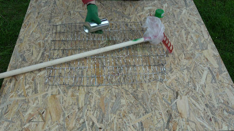 Gardener paint in green new garden rake stick with sprayer Live Action