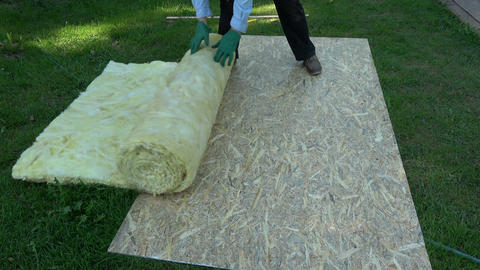 Worker in farm yard rolling new house insulation material Footage