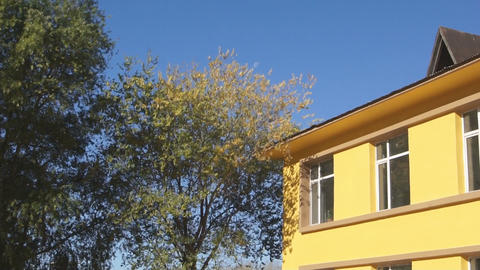 Yellow building corner and trees Stock Video Footage