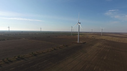 Wind farm with wind turbines in field Footage