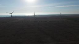 Wind generators working in a field near the sea at high wind farm Footage