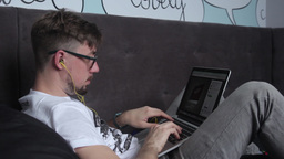 The guy typing on the laptop lying on the couch Footage
