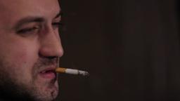 A man smokes a cigarette at night ビデオ