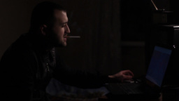 A man smokes a cigarette at night and looks in the laptop monitor ビデオ