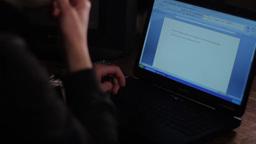 Man typing on a laptop keyboard at night ビデオ