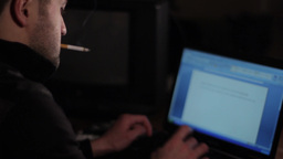 Male writer at night Smoking a cigarette, and prints the story on the laptop key Footage