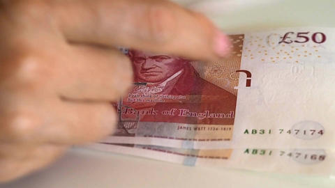 Woman counts for 50 pound banknotes Image