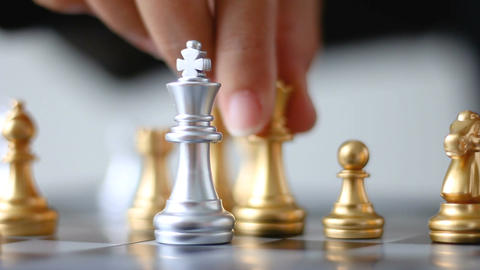 Close up shot hand of business woman moving gold king chess to kill silver king Image