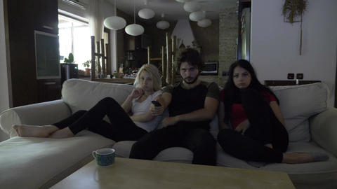 Three friends watching sad movie in the living room sitting on a couch Footage