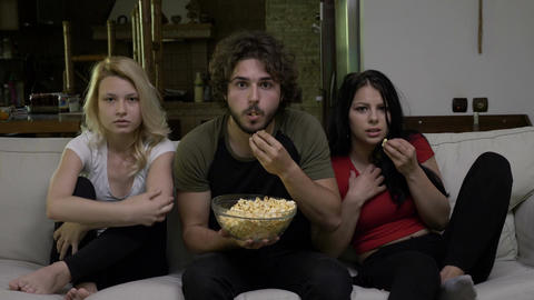 Two young women and a guy eating popcorn and watching horror film with a fear Footage