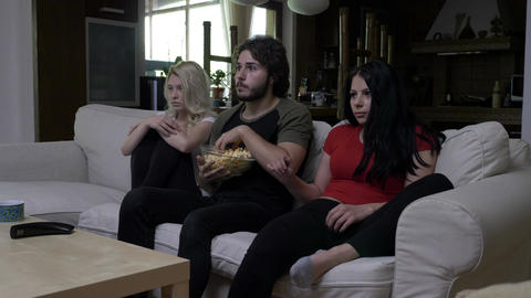 Roommates eating popcorn at home get scared while watching horror movie Footage
