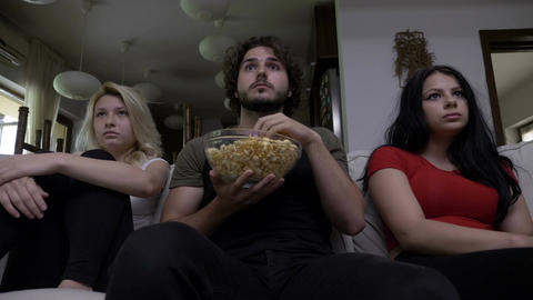 Three friends eating popcorn watch horror movie together and are very captivated Footage