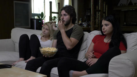 Friends eating popcorn and watching horror movie with very expressive faces Footage