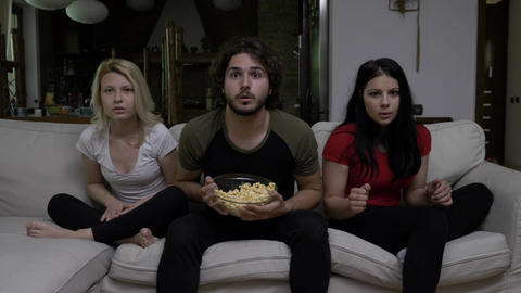 Happy football fans watching game and supporting favorite team while eating Footage