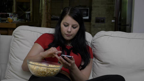 Woman sitting on the couch with a bowl of popcorn in her lap and texting on Footage