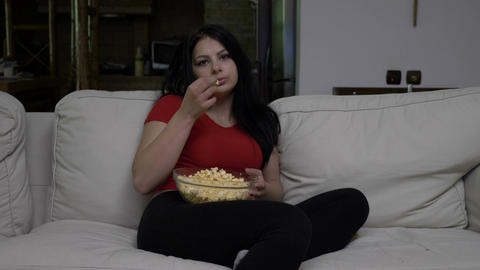 Bored young woman sitting on the couch and eating popcorn while watching TV in Footage