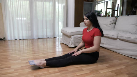 Young woman doing yoga breathing exercise and meditating in lotus position on Footage