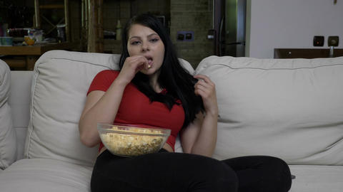 Teen sitting on the sofa and eating popcorn while watching movie and feeling Footage