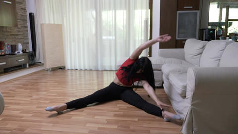 Athletic woman stretches on the floor in her living room at home Footage