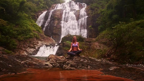 Girl Relaxes in Yoga Position behind Small Lake at Waterfall Footage
