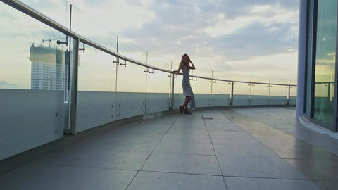 Motion to Girl Standing on Hotel Balcony against Skyscraper Footage