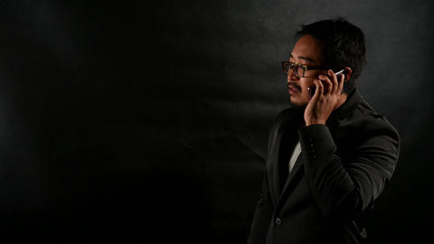 Businessman in Black Suit talking on cellphone on black wall background Footage