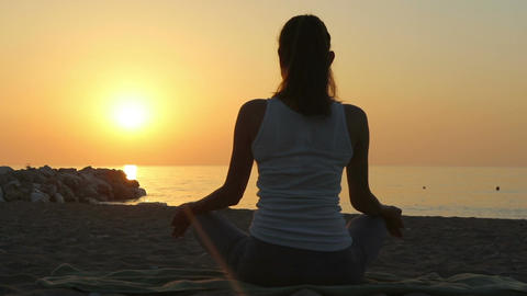 Woman meditates in the morning on the seashore ビデオ