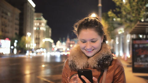 [alt video] Happy Girl Walks and Uses Mobile Smartphone against the...