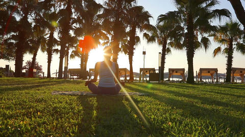Morning meditation in the park, woman practices yoga on the seashore Acción en vivo