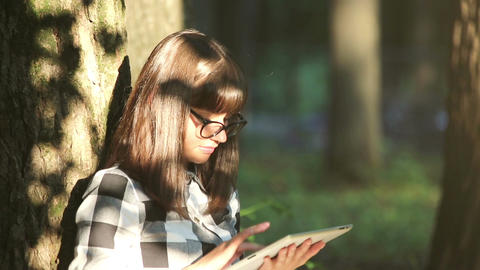 Girl Relaxes in the Park with a Tablet PC Acción en vivo