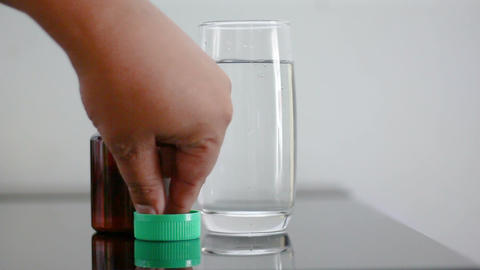 Close up shot hand of man picking and eating drug and water Footage