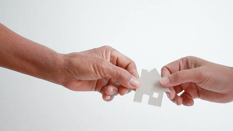 Hand of old women giving paper card house to young woman metaphor and concept Footage