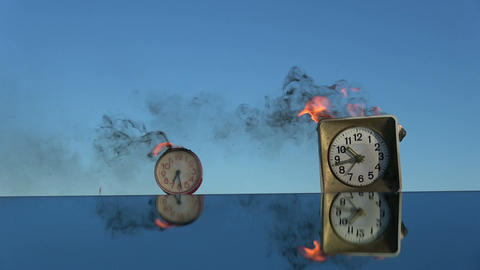 Time is a fire. Burning two old alarm clocks on mirror in space Archivo