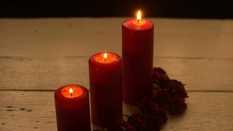 Three red candles light with rose on white table 画像