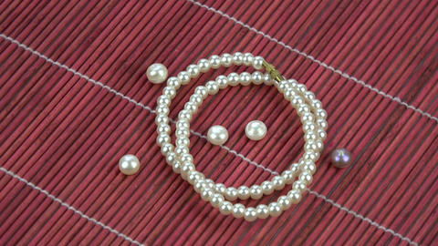 Rotating String of pearls on red bamboo mat background Footage