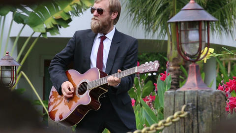 bearded man in black suit plays guitar actively and goes out Footage
