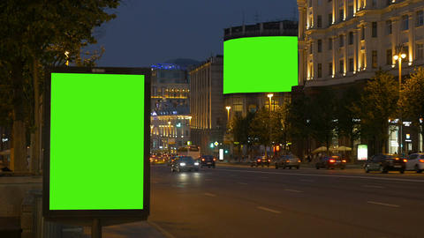 Two billboards with a green screen. In the evening, on a busy street Footage