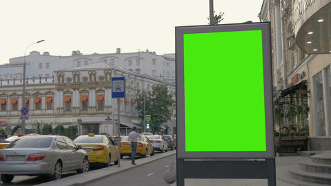 A Billboard with a Green Screen on a Busy Street Footage