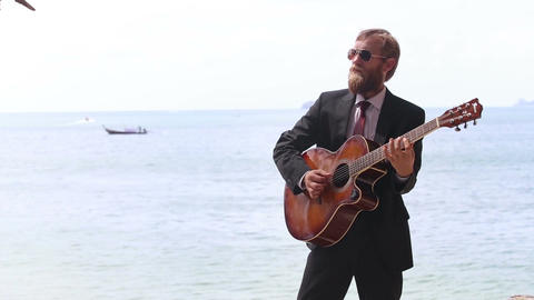 european man plays guitar against sea islands and boat Footage