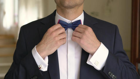 Man Fixes Bow-tie on a Neck and Buttons Jacket Footage