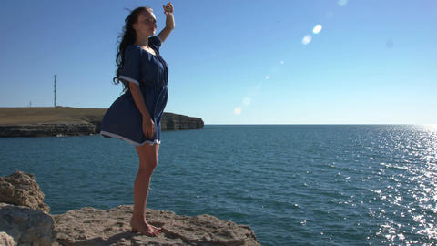 The girl in the blue dress standing by the sea Archivo