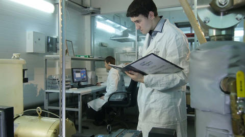 Young Concentrated Laboratory Assistant Makes Notes in Folder Footage