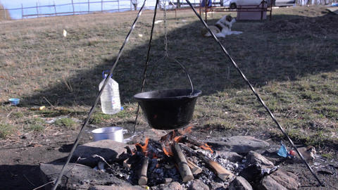 Man prepares to make a stew kettle. He made fire wood, put the kettle on the fir Footage